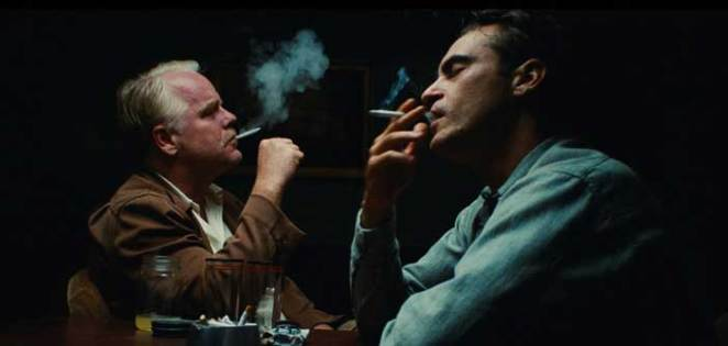 Phillip Seymour Hoffman and Joaquin Phoenix smoke in a black room