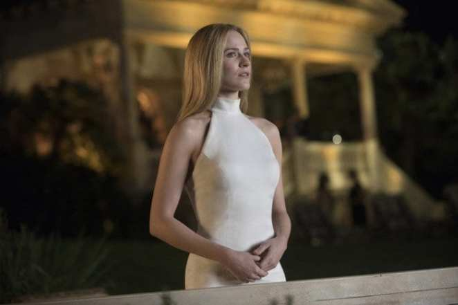 Dolores, wearing a white dress, attends a party in a flashback