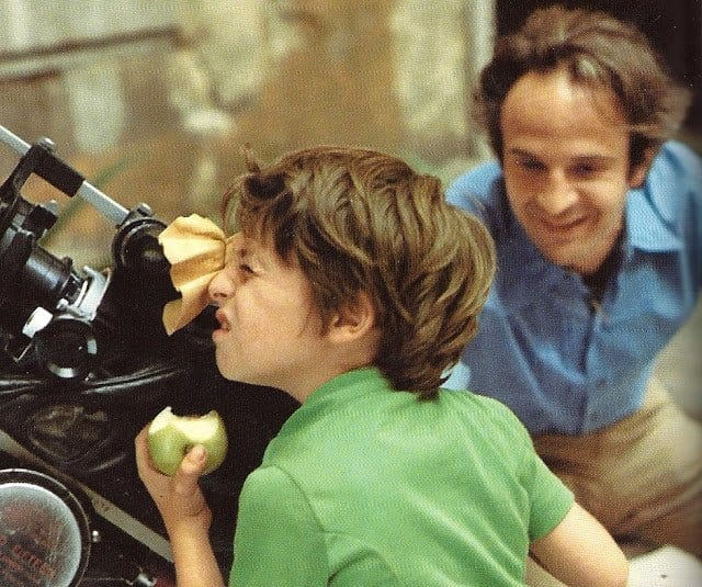 Truffaut with a boy looking through a telescope while eating an apple
