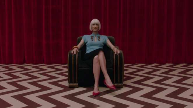 Diane Evans, sitting with her legs crossed, on a chair in the red room, chevron floor pattern and red curtains behind her.