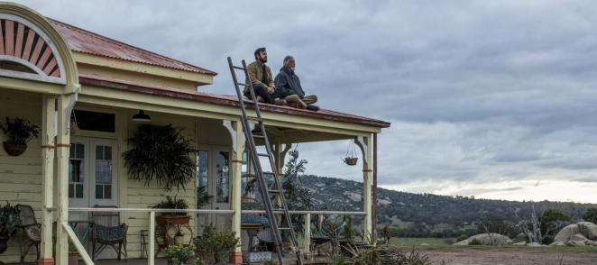 Kevin Sr. sits with his son on the roof of a house in Australia after the rain