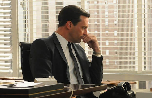 Don Draper with his hand to his chin looking worried in Mad Men