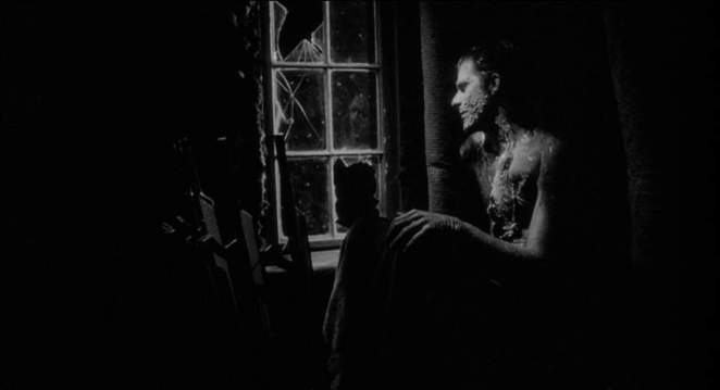 A mutated man sits in the dark looking out of a broken window