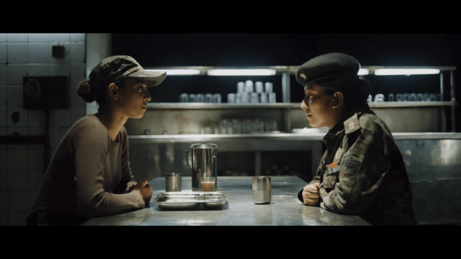 a female and male army officer sit opposite each other in a dark cafeteria kitchen