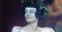 a woman with a startled eye mask and ringlet hair in Satyricon