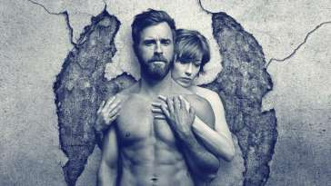 Nora holds her hands on Kevin's bare chest in front of a broken wall that looks like angels' wings