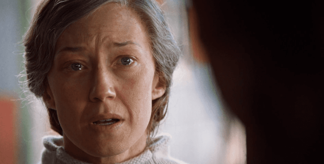 A grey haired Nora has a tear in her eye as she talks to Kevin