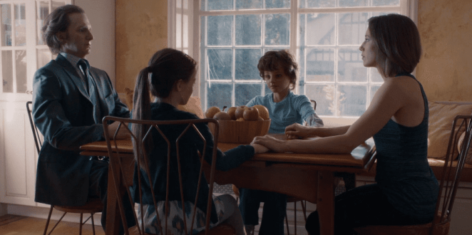 Nora sits at her table with Loved Ones replicas of her family
