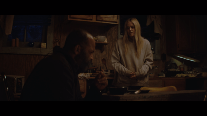 2 people talk in a dark kitchen in Hold the Dark