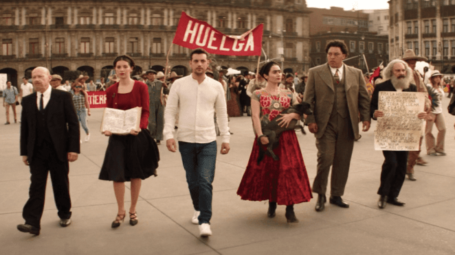 six figures walk across a paved surface dressed as characters from a diego rivera mural