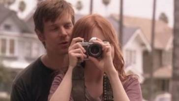 Nate stands behind Claire, who is looking through a camera