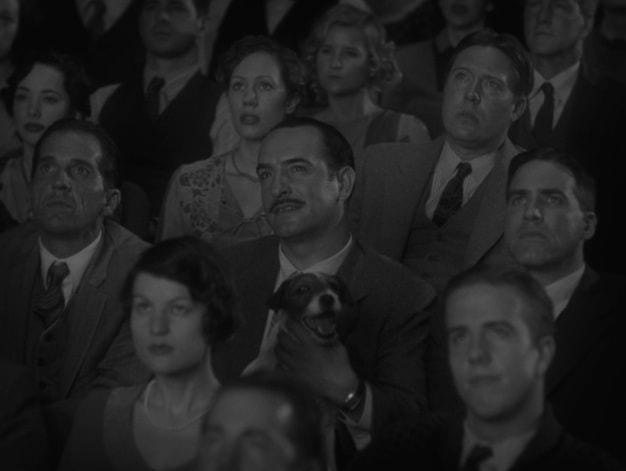 Jean Dujardin as George Valentin with Uggie the dog on his lap in a theatre audience in The Artist
