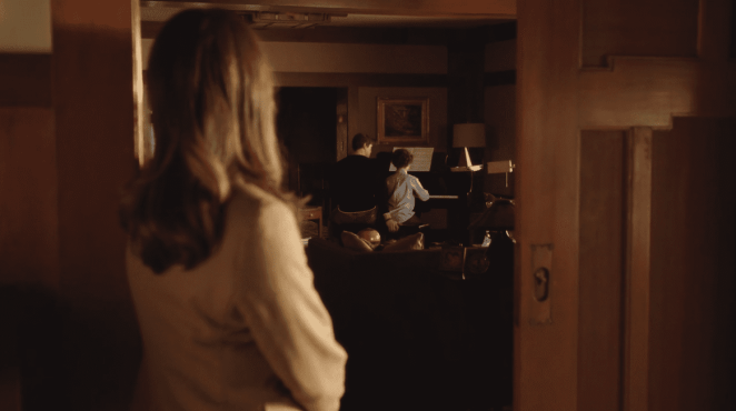 "Katherine Ford (Diane Lane) looks on as David Patton (Andrew Rannells) questionably places his hand at the end of The Romanoffs ""Bright and High Circle"""
