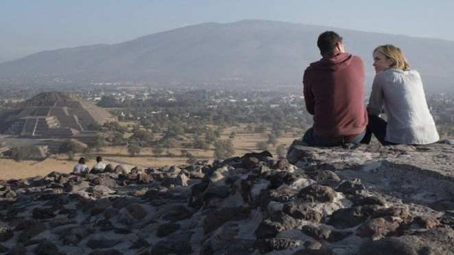 a man and a woman sit overlooking Mexican pyramids at Teotihuacan