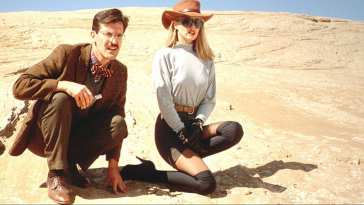 A man and woman crouch on sand in the sun, in Sundown: The Vampire in Retreat