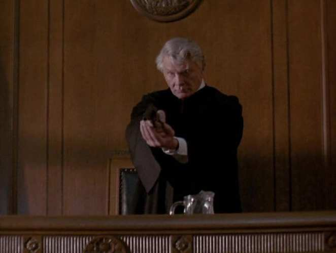 Steve Forrest as Judge Murdoch holding a gun in his bench