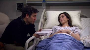 a man reads a book to a woman sick in a hospital bed
