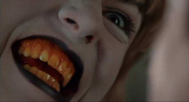 Laura Palmer with a white face, black lips and yellow teeth