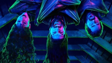 Vampires hanging upside down and showing their fangs