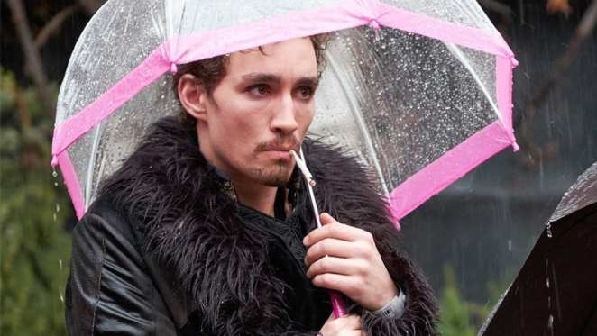 Robert Sheehan as Klaus Hargreeves standing in the rain under an umbrella