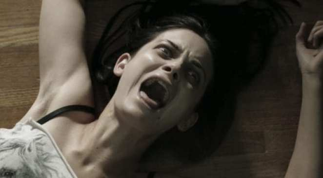 Stevie is possessed and screams as she is dragged along the floor in The Pact