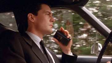 Agent Cooper speaking into his recorder, entering Twin Peaks