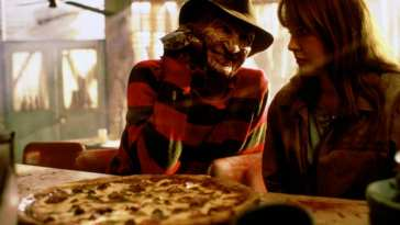 Freddy Krueger (Robert Englund) and Alice (Lisa Wilcox) share a pizza.
