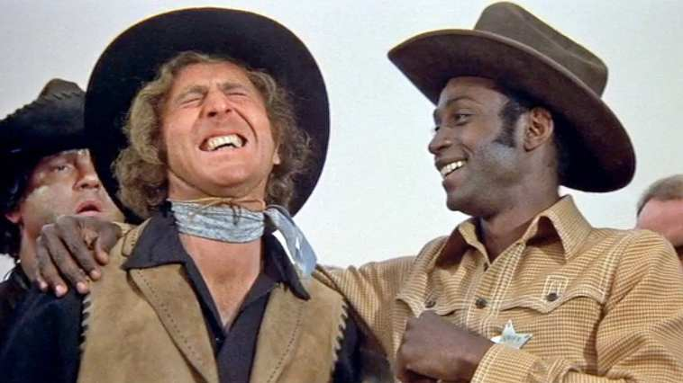 Gene Wilder and Clevon Little laughing together in Blazing Saddles