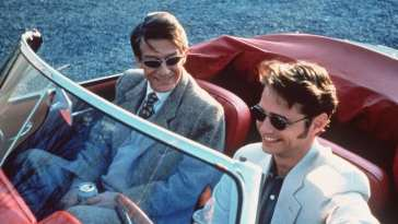 Giles and Ronnie in a car, sharing a laugh