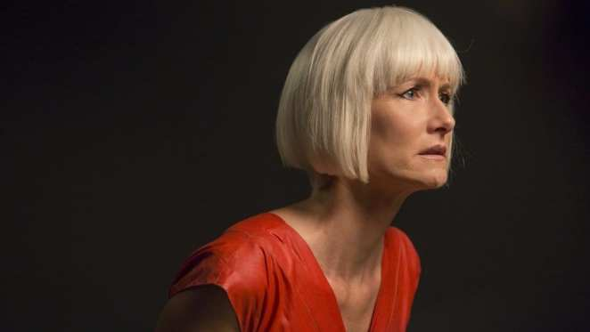 Diane Evans played by Laura Dern in Twin Peaks wearing a red top and standing in the dark