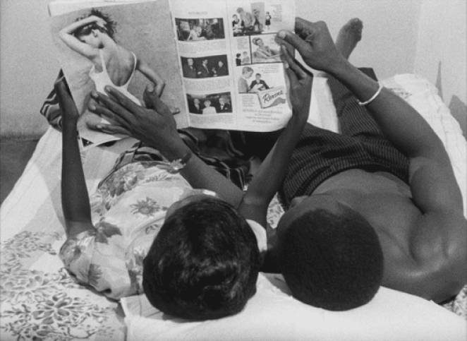 A couple in Dakar, Senegal in the 1960s look at a French magazine