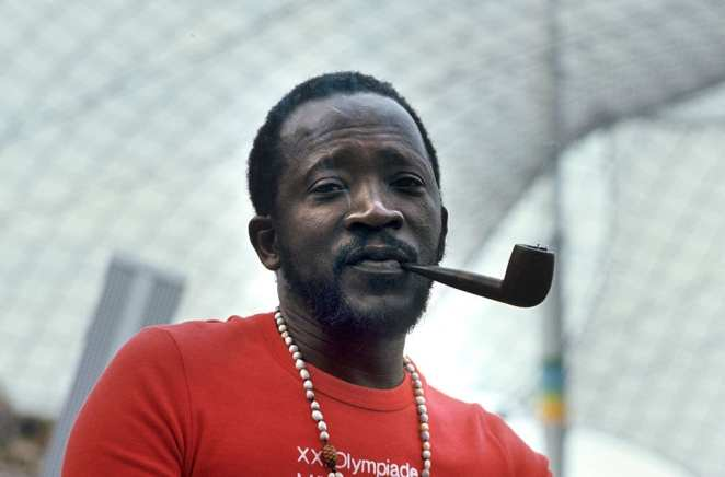 Senegalese author and filmmaker Ousmane Sembène with a pipe in his mouth.