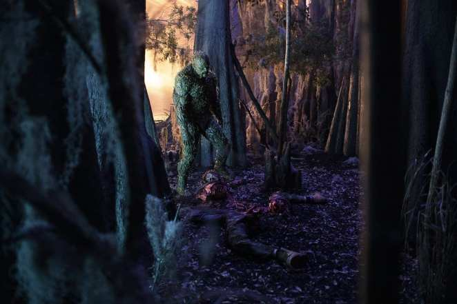 Swamp Thing (Derek Mears) stands over the body of the first person he has killed.
