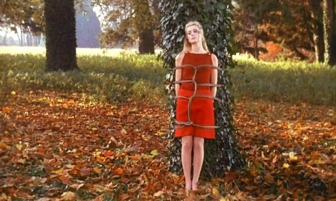 Séverine in a red dress is tied to a tree outside during one of her sexual fantasies