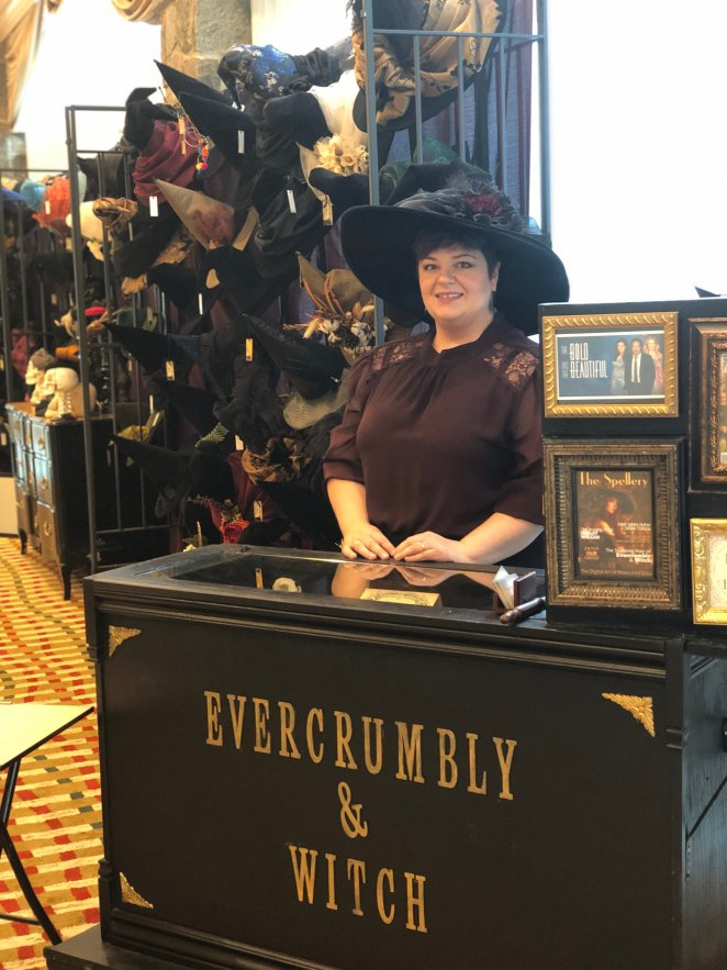 The proprietor of vendor Evercrumbly and Witch, at her booth, selling witch's hats