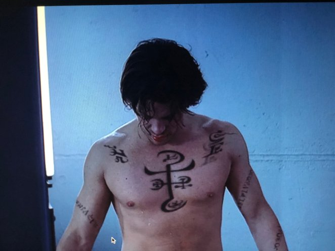 Lindsey, shirtless and a little bloody, watches as his protective tattoos disappear.