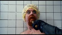 A man in a shower with a shower cap on with a mystery hand pushing a plunger over his mouth