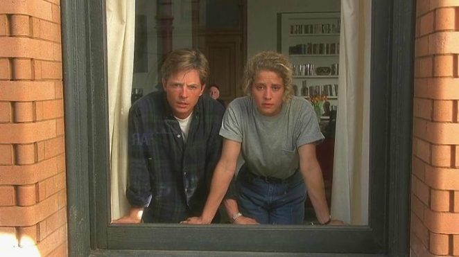 A man and a woman look out of a window with confused looks on their faces