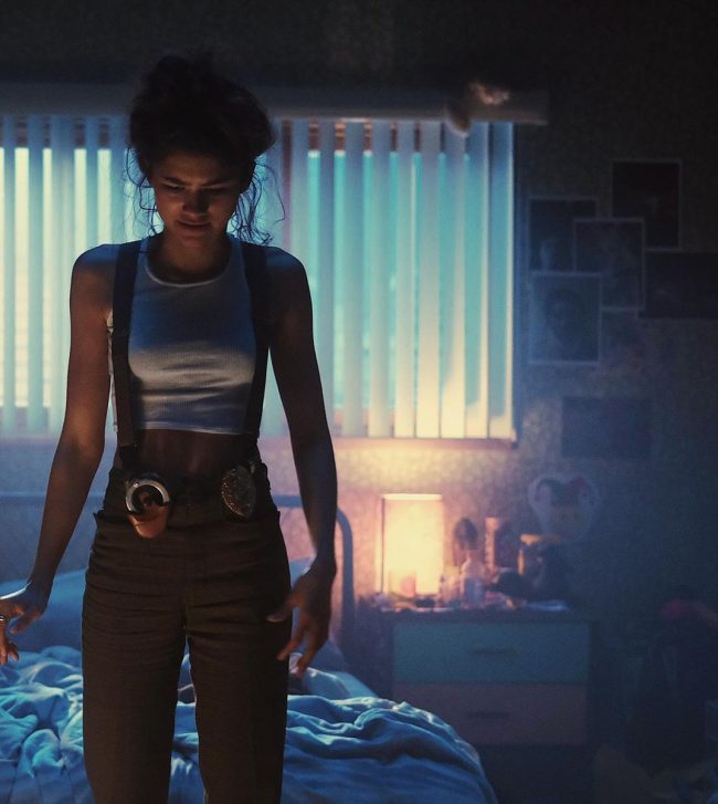 Rue standing in her bedroom while wearing a gun holster, handcuffs, and police badge on her hip.