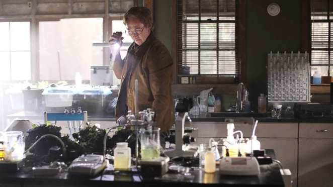 Dr. Jason Woodrue (Kevin Durand) searches Alec Holland (Andy Bean)'s lab for proof of the Swamp Thing's existence.