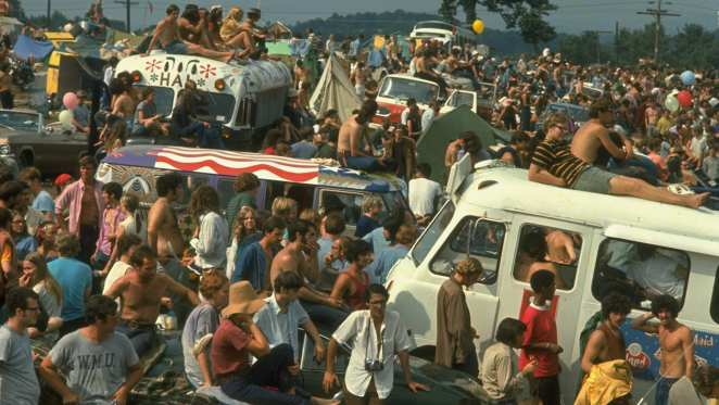 colour image of Woodstock festival attendees crowding around vehicles on the festival site