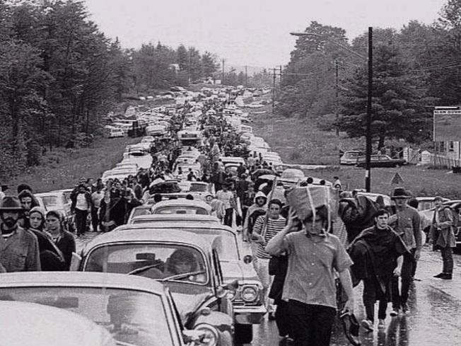 black and white photo of traffic jam with cars and people crowding a highway leading to Woodstock