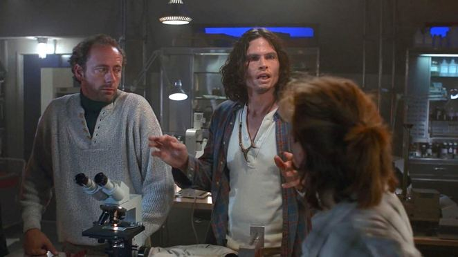 One hostile-looking man talking to two other people in a lab.