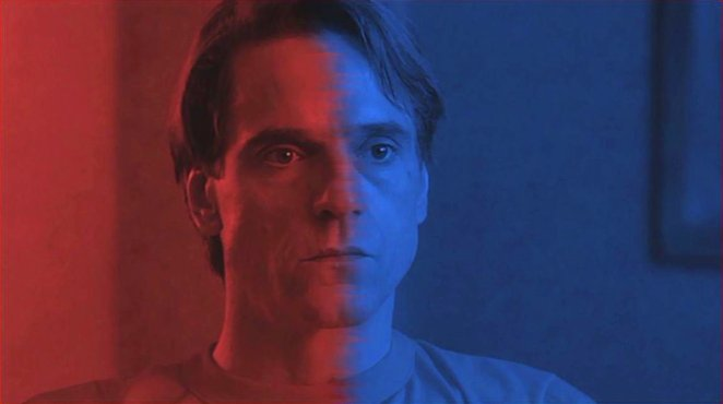 Jeremy Irons face half lit in red half in blue in Dead Ringers