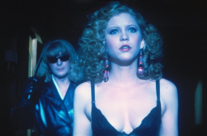Woman in lingerie is about to be attacked by a man disguised as a woman wearing a blonde wig and black sunglasses.