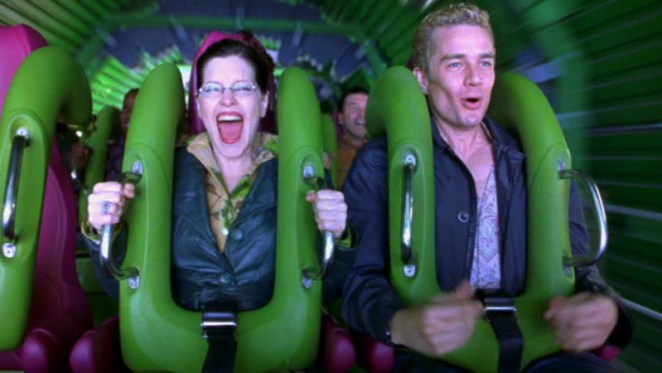 A news reporter and her cameraman enjoy a rollercoaster, the latest entertainment from amusement park mogul Stephen Price.