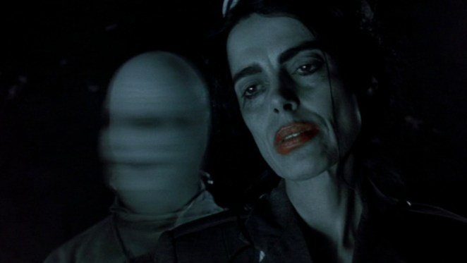 Two ghosts from House on Haunted Hill. One is a nurse with a pale face, dark eye shadow, and bright red lipstick. The other is a doctor whose face shakes violently back and forth.