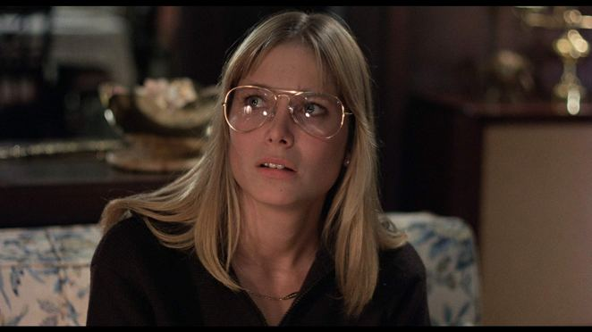 Deborah Raffin in God Told Me To (1976) wearing glasses and looking confused