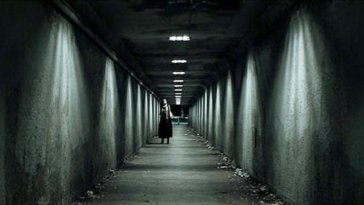 a woman walking down a tunnel at night
