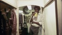 Pierce Mundy (Everett Silas) has a drink and leans in the doorway of his parents' dry cleaning shop.